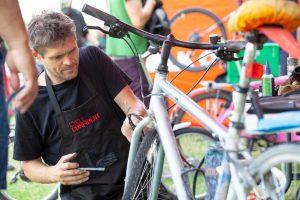 Bike mechanic fixing a silver bike at Le Tour de Waltham Forest 2018